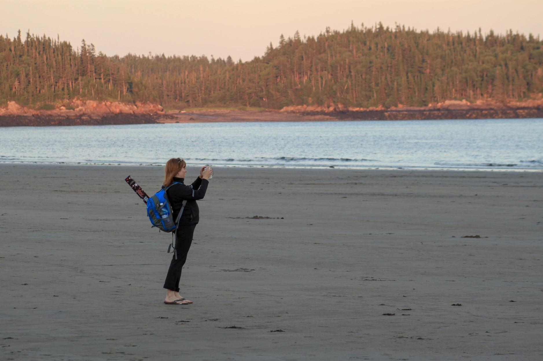 A person holding a surfboard on a beachDescription automatically generated with medium confidence