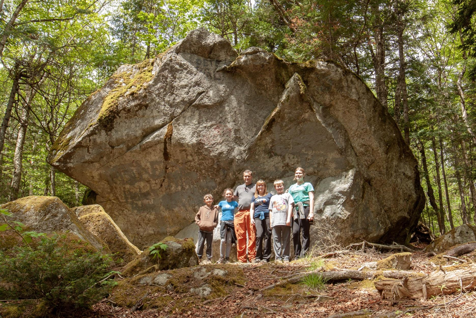A group of people standing next to a large rockDescription automatically generated with medium confidence